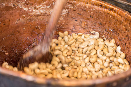 Almonds are roasted by hand - close-up stirring in a pot Stock Photo