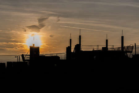atmospheric glowing sunset on a construction site silhouette Stock Photo