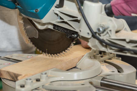Joiner cuts piece of wood in workshop with saw - miter saw