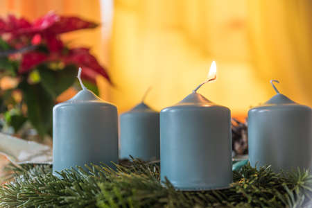 first candle on Advent wreath is burning - atmospheric candlelight on Advent wreath