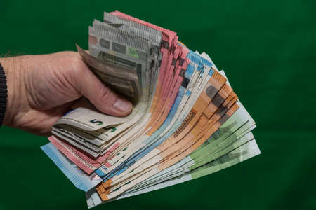 Close-up of a handful of euro bills - money handing paper money Stock Photo