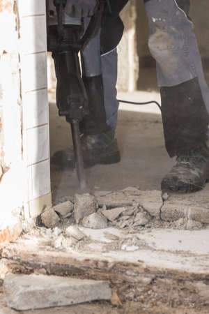 Worker with a demolition hammer while cramming - chiseling close-up 写真素材