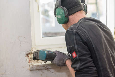 Worker on construction site with tool during remodeling and renovation work - close-up