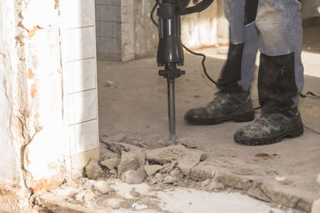 Worker on construction site with a demolition hammer - closeup of concrete chisel