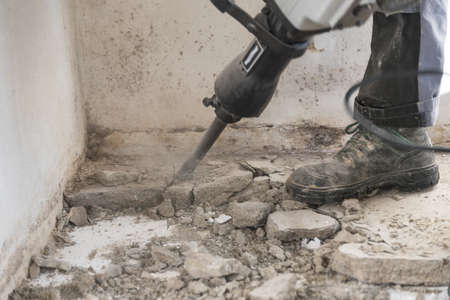 Construction worker cramps concrete on construction site with demolition hammer - chiseling close-up 写真素材