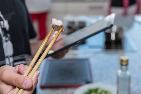 Cooking instruction through digital cookbook - closeup of chopsticks with meat and tablet