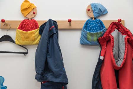 Kindergarderobe mit kindgerechten Kleiderhaken und Kinderjacken - Nahaufnahme Standard-Bild