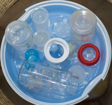 Czyszczenie butelek dla niemowląt w sterylizatorze parowym - zbliżenie sterylizujących przyssawek, smoczków, butelek Zdjęcie Seryjne