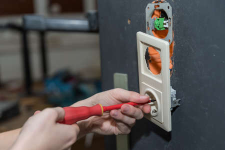 Electrician installs electrical outlet on the wall with screwdriver - closeup skilled worker Banque d'images