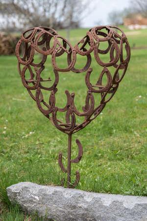 Horseshoe heart as garden decoration - 3-D metal heart and love symbol Stock Photo