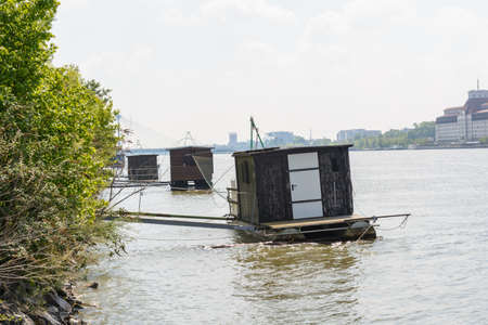 simple wooden boat on the shore - wooden hut serves as houseboat