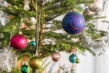 Colorful Christmas tree balls and other decoration at the Christmas tree - close-up
