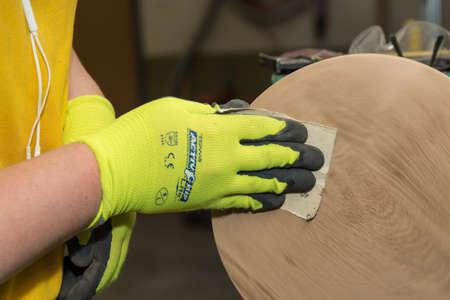 Carpenter sanding turned wooden discs with fine sandpaper - Close-up joiner