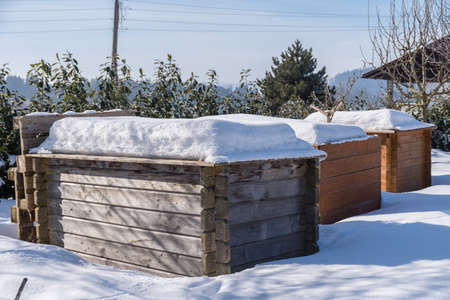 snowy garden with snowy raised wooden ramparts - upcycled raised bed