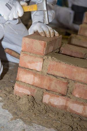 Craftsman in building a brick wall with small bricks and masonry hammer - close-up
