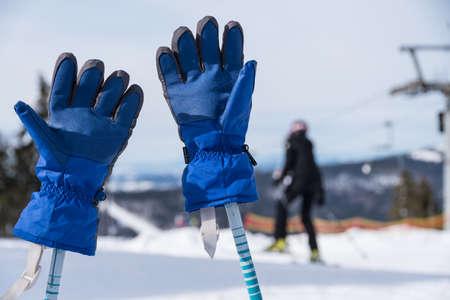 Ski gloves stuck on ski poles in snowy ski resort - close-up Stock Photo
