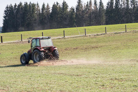 Farmer with tractor and agricultural machinery scarifying - farmer doing field work Stok Fotoğraf