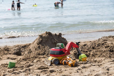 Children's toys and sand castle on the sandy beach during a beach holiday - vacation trip