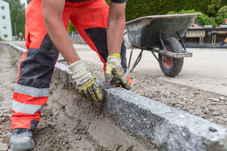 Road workers with mortar while laying curbs - close-up of craftsman