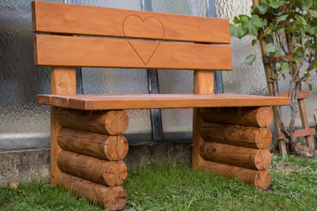 stable solid wood bench with engraved heart for lovers in the garden Фото со стока