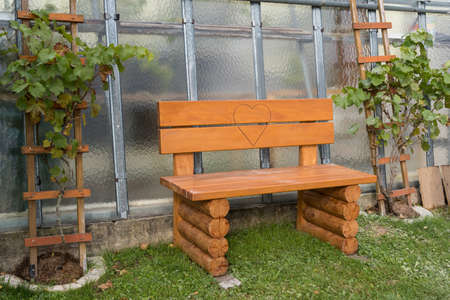 Solid wooden bench with a heart in the garden for lovers - garden bench