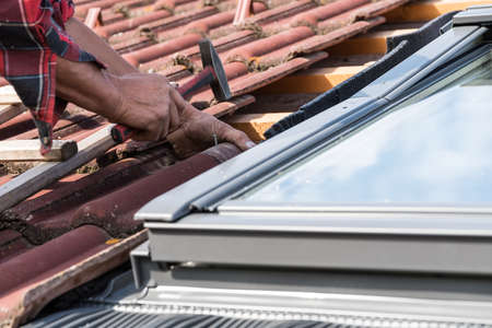 Roofers on the roof installing a roof window - close-up craftsman