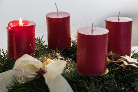 Advent wreath with atmospheric light from the first candle - close-up