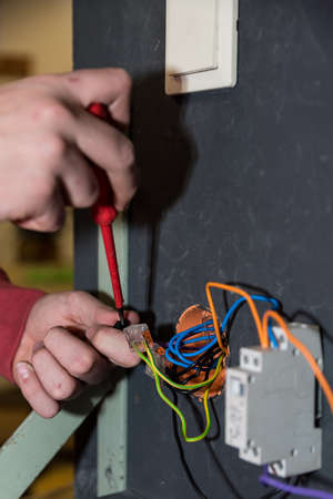 Electrical engineer installs switch, socket and relay - close-up