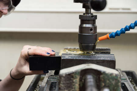 Craftswoman works metal with step drill of the drill - close-up
