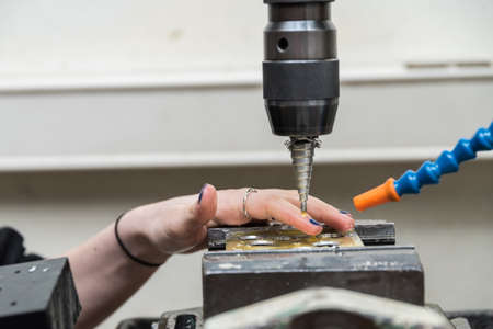 Skilled worker works with drill for metalworking in the metal industry - close-up