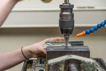 Craftswoman at drilling machine with step drill - close-up metalworking Standard-Bild