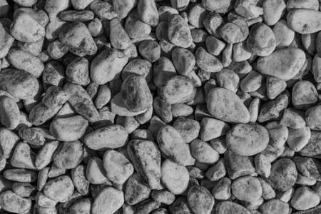 black-and-white background with round gravel - roll gravel, drainage gravel