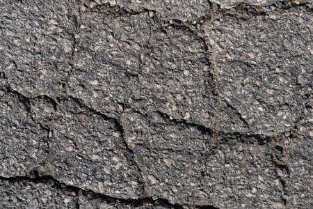 irregular cracks in the asphalt - background and pattern Standard-Bild
