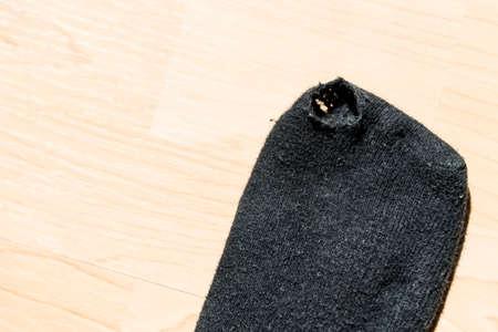 Hole in a black sock - detail, copy space Standard-Bild