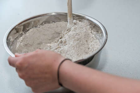 To bake bread, mix the flour into the dough with a wooden spoon - close-up Stock Photo