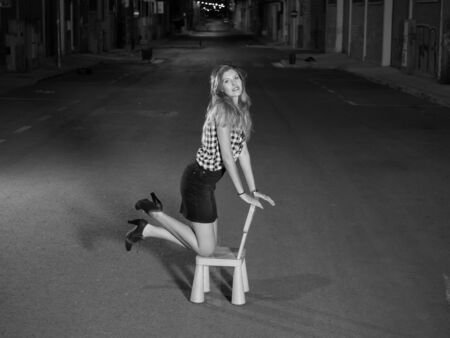 woman kneeling: pretty blonde woman kneeling in child seat in the street at night