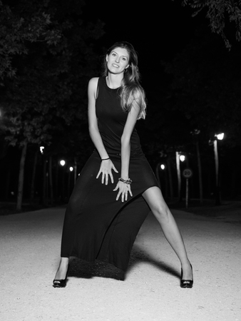 spread legs: white and black woman with black evening dress outdoors Stock Photo
