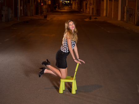 woman kneeling: pretty blonde woman kneeling in child seat in the street at nigh
