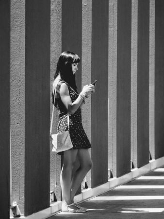 twentysomething: young woman addicted to mobile phone in monochrome