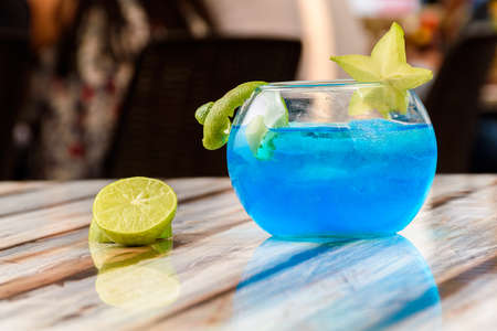 blue drink with kiwi and lemon served in a large glass