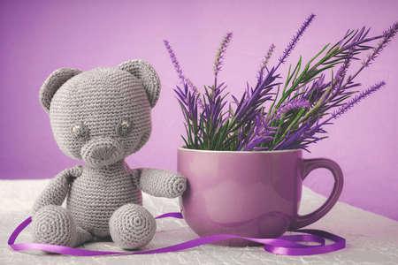 Oso de juguete tejido de estambre, al lado de una taza decorada con lores artificiales Foto de archivo