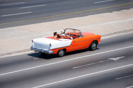 Tourists on board a classic American convertible car from the 50s driving along the Malecon in Havana, Cuba Stock Photo