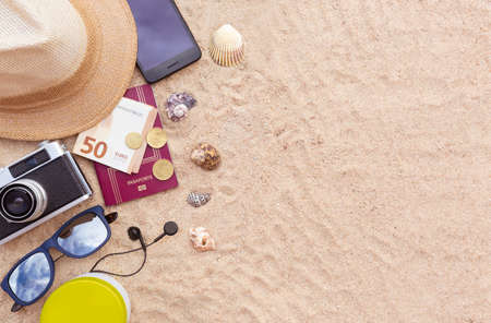 Some beach items, a passport and some cash, a smartphone, hat, camera and sunglasses on the sand. Space for text. Holiday, summer and beach concept.