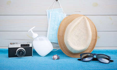 Protective face mask, hand gel, straw hat and photo camera on blue towel and wooden background. Vacation concept during the Covid-19