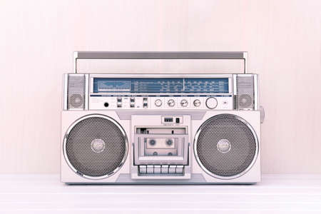 80's retro cassette radio in silver colour on light wood background. Play music concept.