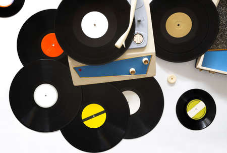 Portable turntable from the 60s and different vinyl records on white background. Play music concept.