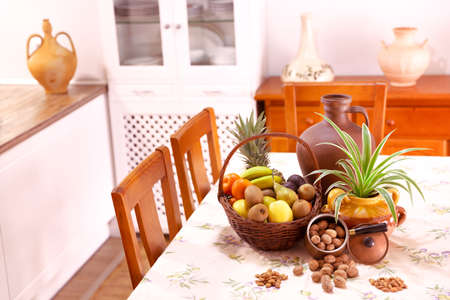 Rustic design kitchen with basket of fruits, plants and nuts on the table. Decoration concept.