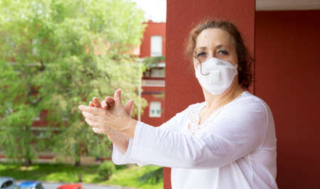 Portrait of old woman wearing medical mask applauding from the balcony in gratitude to the health workers. Confinement by coronavirus. Covid-19 concept.