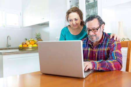 A couple of smiling seniors using a laptop computer at home.  Adaptation to the technology of older people concept. Stock fotó - 149429568