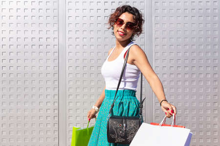 Young, smiling woman walking with her shopping bags outside a shopping centre. Space for text. Shopping concept.